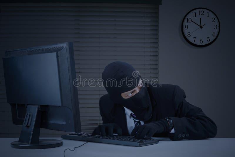 Lo scassinatore prende le informazioni in ufficio immagini stock