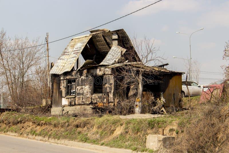 Lo scheletro di una casa di legno bruciata, un edificio residenziale dopo un fuoco, senza trattamento immagine stock libera da diritti