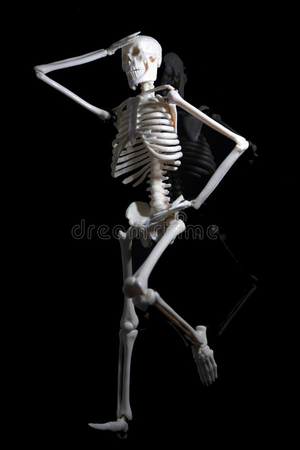 Lo scheletro preoccupato sul piatto nero di riflessione immagini stock