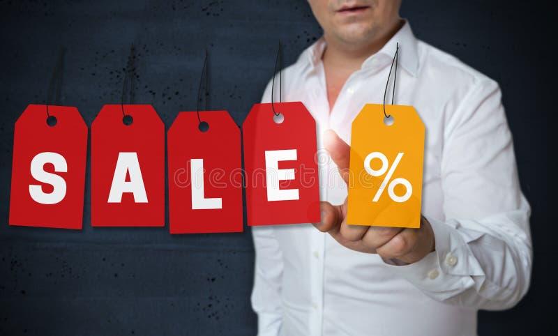Lo schermo attivabile al tatto dell'etichetta di vendita è azionato dal concetto dell'uomo immagine stock