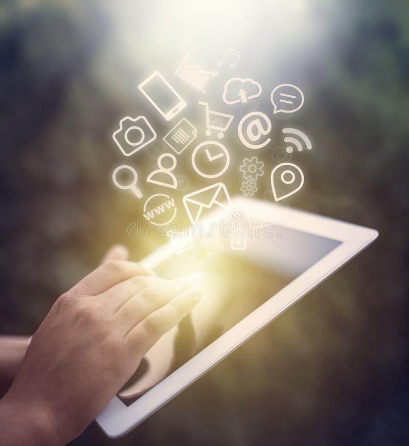 Lo schermo di computer femminile della compressa commovente della mano e le icone di app volano immagine stock