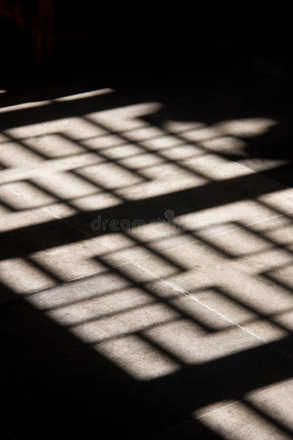Lo schermo di legno decorato getta l'ombra interessante sul pavimento di pietra immagine stock libera da diritti