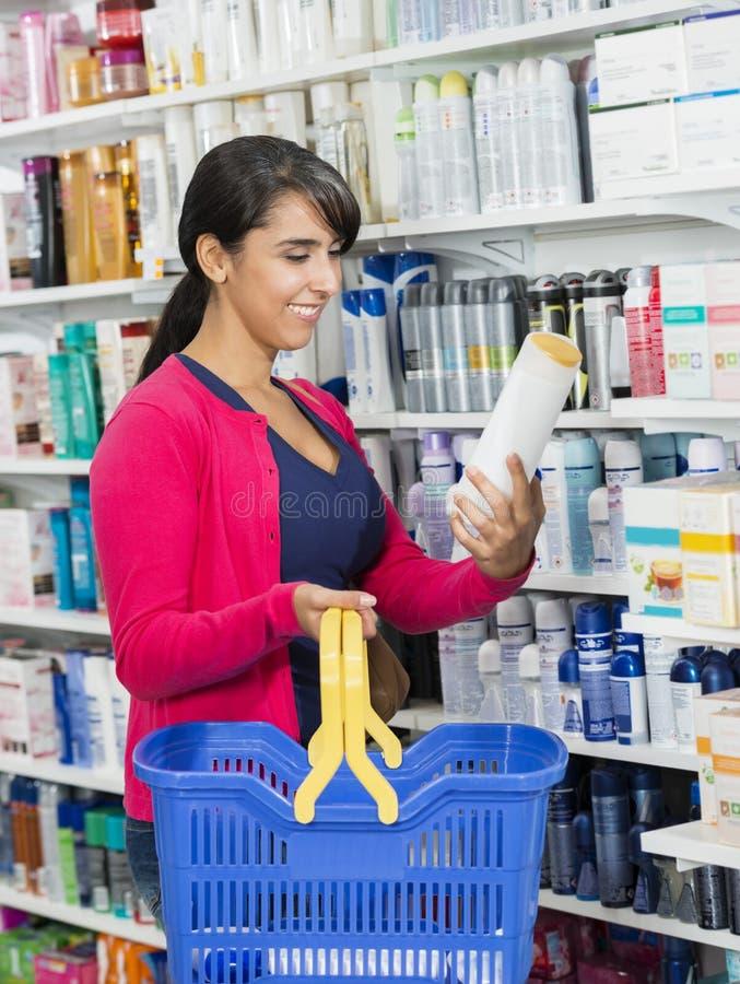 Lo sciampo della tenuta del cliente imbottiglia la farmacia fotografie stock libere da diritti