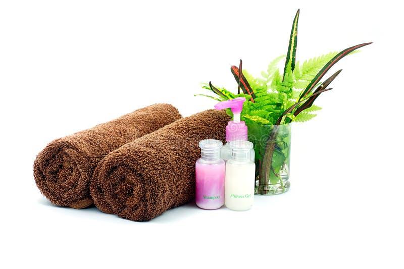 Lo sciampo e la doccia gelificano le bottiglie ed asciugamano e foglie verdi marroni fotografia stock libera da diritti