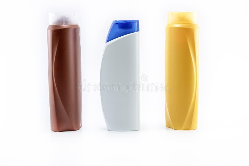 Lo sciampo, idratante imbottiglia i colori marroni, bianchi, gialli Fucilazione nel fondo bianco fotografia stock libera da diritti