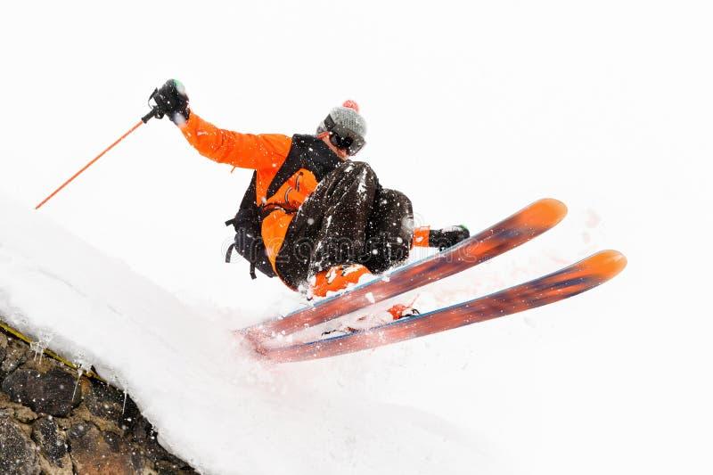 Lo sciatore dell'atleta su un fondo leggero con un salto si muove fuori dal tetto di una capanna innevata con i fiocchi di volo d fotografia stock