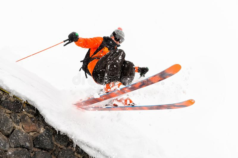 Lo sciatore dell'atleta su un fondo leggero con un salto si muove fuori dal tetto di una capanna innevata con i fiocchi di volo d immagine stock libera da diritti