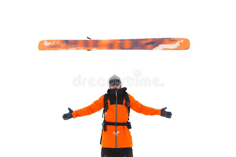 Lo sciatore maschio professionista getta uno sci sopra i suoi braccia che spandono le sue mani per isolare su un fondo bianco Cor fotografia stock