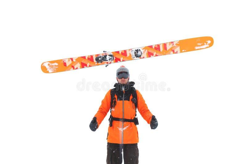 Lo sciatore maschio professionista getta uno sci sopra i suoi braccia che spandono le sue mani per isolare su un fondo bianco Cor immagine stock
