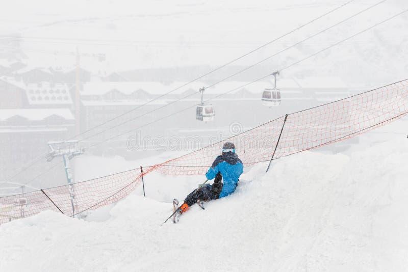 Lo sciatore si siede su un pendio durante le precipitazioni nevose pesanti immagini stock
