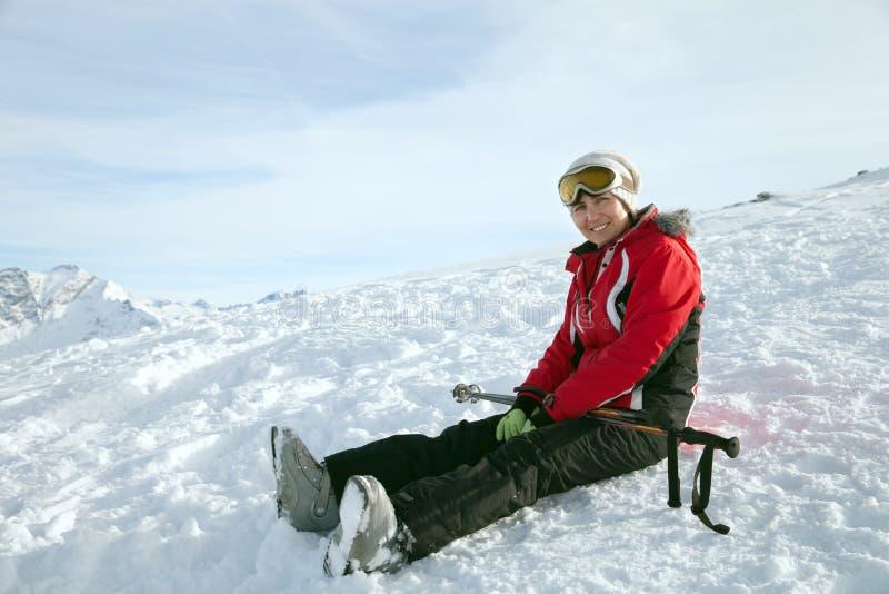 Lo sciatore si siede sul pendio della neve fotografia stock