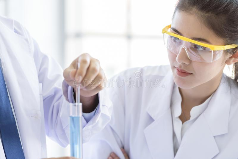 Lo scienziato asiatico dello studente del yound che ricerca e che impara con lo scienziato senior ha fondo d'istruzione in un lab fotografia stock