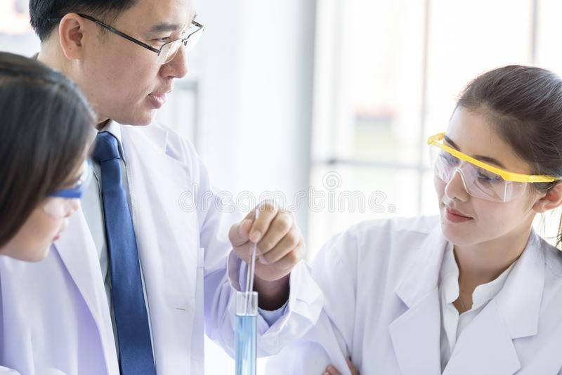 Lo scienziato asiatico dello studente del yound che ricerca e che impara con lo scienziato senior ha fondo d'istruzione in un lab fotografie stock