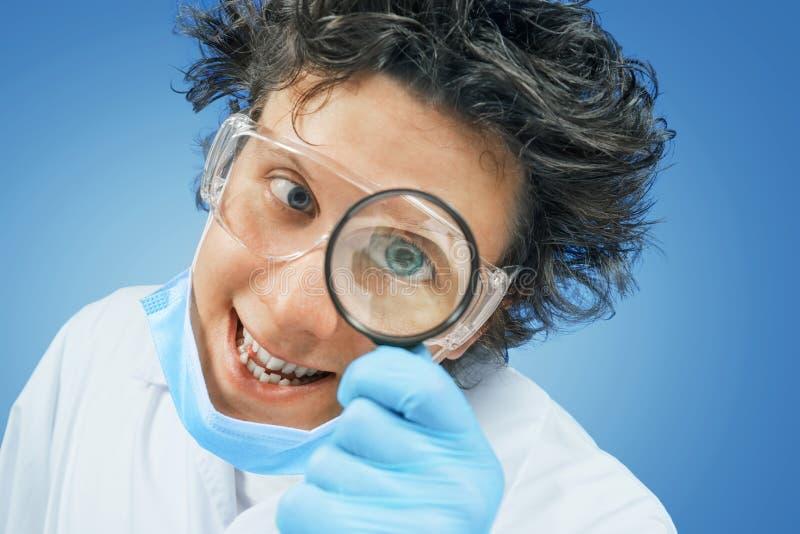 Lo scienziato bizzarro guarda tramite una lente d'ingrandimento fotografia stock