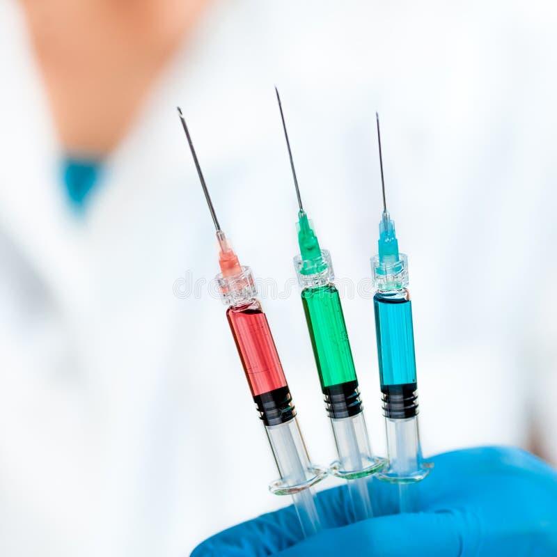 Lo scienziato giudica l'iniezione tre riempita di verde, di rosso e blu fotografia stock