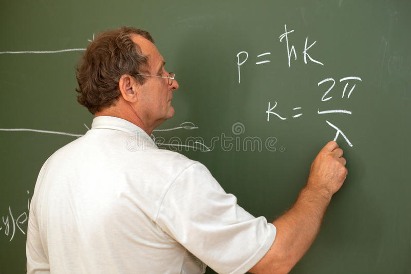 Lo scienziato risolve l'equazione sulla lavagna immagine stock