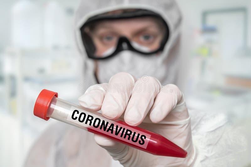 Lo scienziato tiene una provetta sul CORONAVIRUS COVID-19 fotografia stock libera da diritti