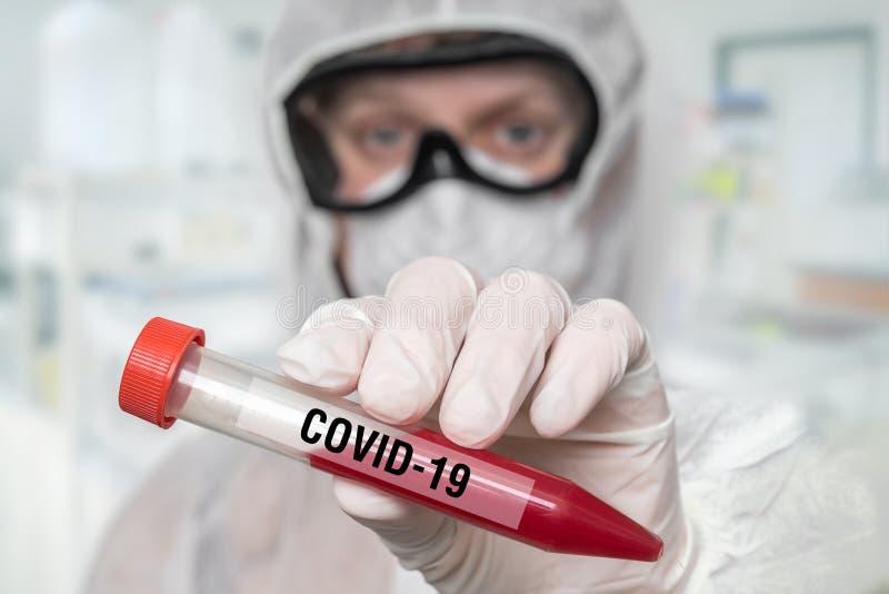 Lo scienziato tiene una provetta sul CORONAVIRUS COVID-19 immagini stock