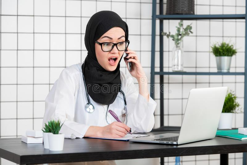 Lo scienziato velato femminile che si siede sul suo scrittorio che esamina il computer portatile apre la sua bocca con emozione c fotografia stock