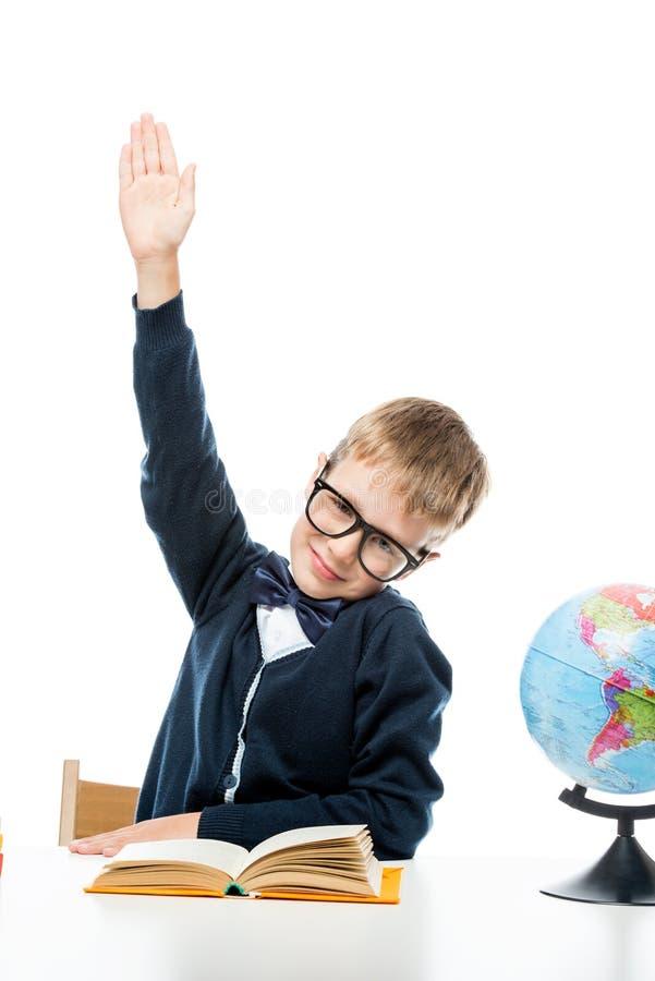 lo scolaro astuto tira il suo braccio mentre si siede immagine stock