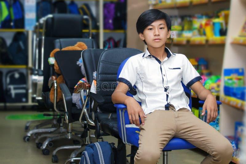 Lo scolaro del ragazzo del ritratto del ritratto l'asiatico dello zaino che del negozio dell'affare si siede uno fornisce lo stud fotografia stock