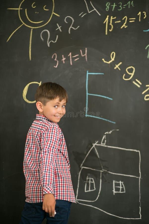 Lo scolaro disegna il gesso su un consiglio scolastico immagini stock