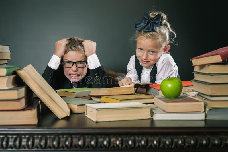 Lo scolaro nello sforzo o nella depressione all'aula della scuola, scolara aiuta fotografia stock