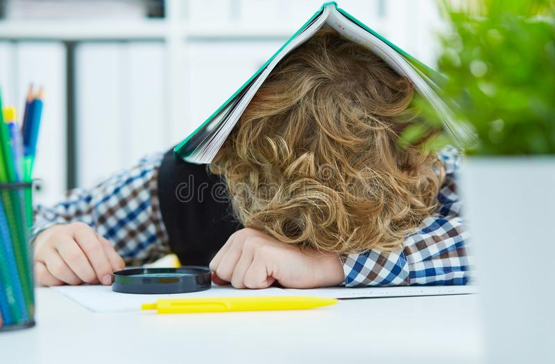 Lo scolaro stanco sta sedendosi ad uno scrittorio con la testa sul tablewith il taccuino sulla testa fotografia stock libera da diritti