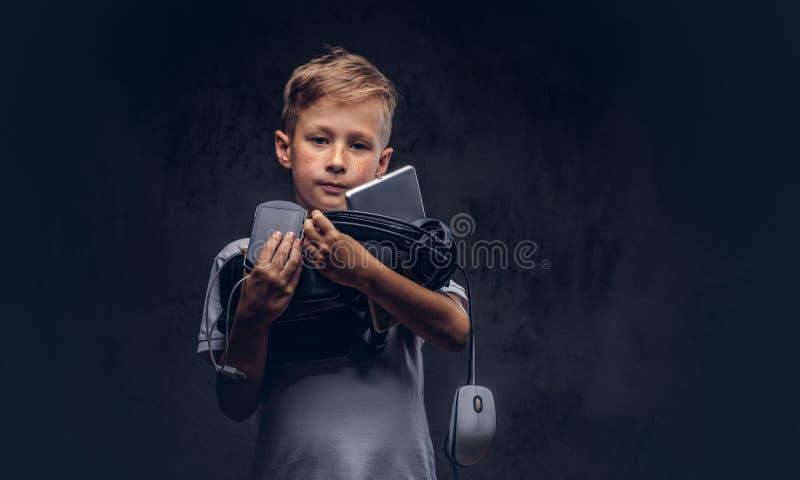 Lo scolaro sveglio si è vestito in una maglietta bianca, tiene l'insieme digitale completo per spettacolo ad uno studio su buio fotografia stock
