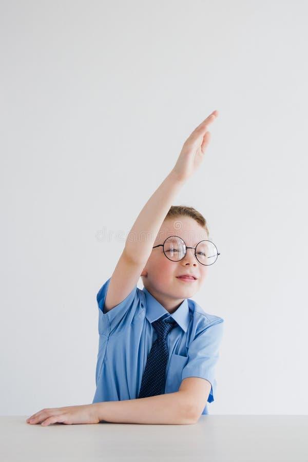 Lo scolaro in uniforme scolastico e vetri solleva la sua mano alla D immagine stock