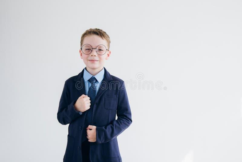Lo scolaro in uniforme scolastico e vetri sta su un fondo o fotografia stock