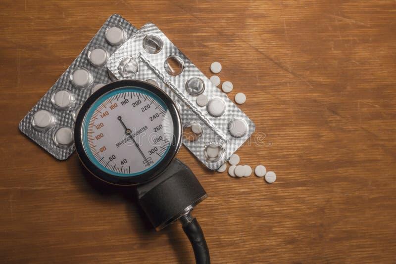 Lo sfigmomanometro con medicina bianca droga su una superficie di legno fotografia stock
