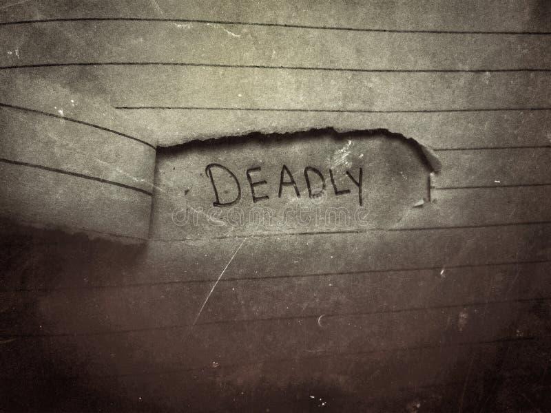 lo sfondo di una parola mortale scritta a matita sulla pagina di carta tagliata fotografie stock libere da diritti