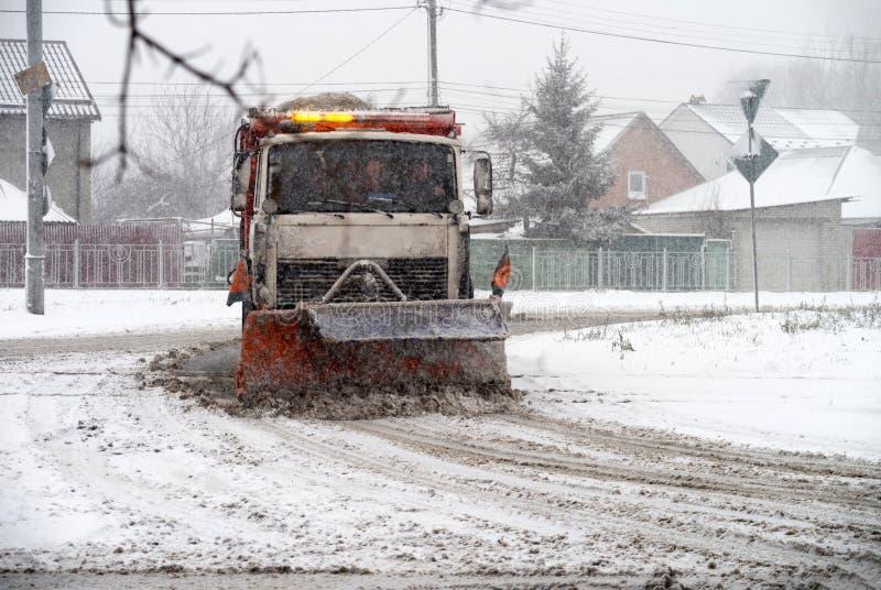 Lo sgombraneve a turbina pulisce la strada nella città durante la bufera di neve fotografia stock