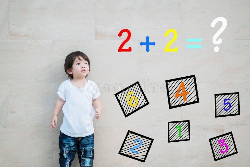 Lo sguardo asiatico del bambino del primo piano alla domanda matematica sulla parete di pietra di marmo ha strutturato il fondo immagine stock
