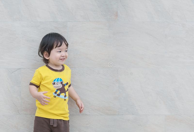 Lo sguardo asiatico sveglio del bambino del primo piano allo spazio con il fronte di sorriso sulla parete di pietra di marmo ha s immagine stock libera da diritti