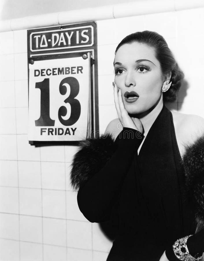 Lo sguardo della giovane donna ha colpito dopo avere visto venerdì il tredicesimo su un calendario (tutte le persone rappresentat fotografia stock libera da diritti