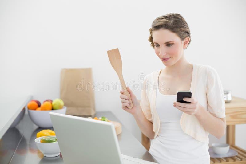 Lo sguardo della giovane donna si è concentrato al suo computer portatile che tiene il suo smartphone immagine stock