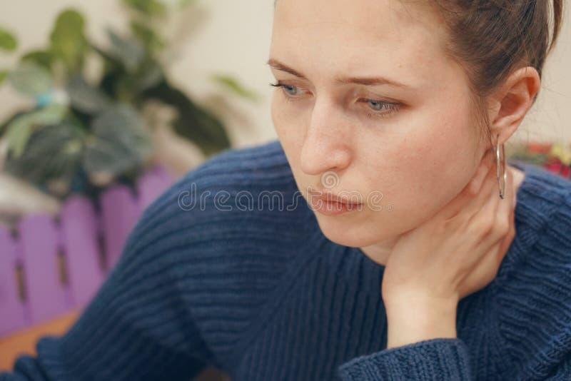 Lo sguardo fisso messo a fuoco donna tiene il suo collo, fotografia stock libera da diritti