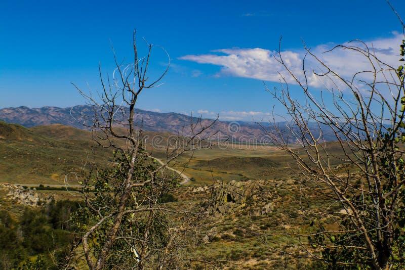 Lo sguardo possiede su terreno e strada e moutains rocciosi collinosi nella distanza negli altopiani dell'Idaho immagini stock