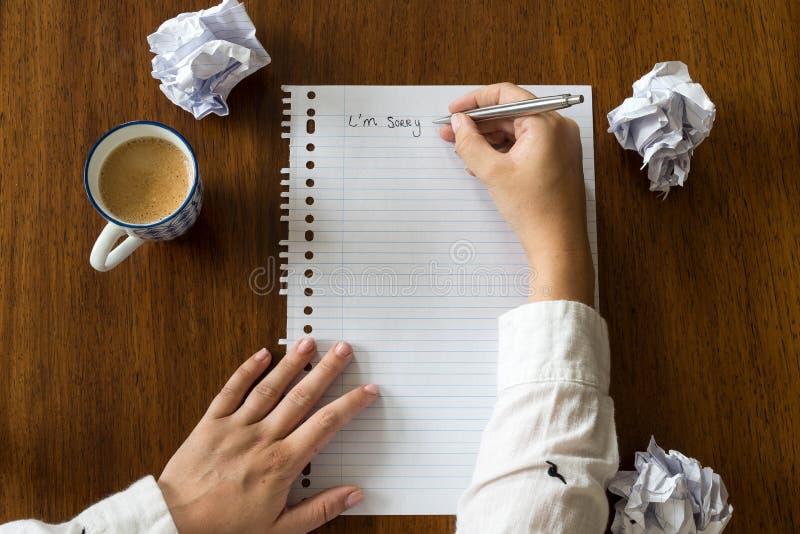 Lo siento escrito en el papel con café en las manos de madera de la tabla de una persona foto de archivo libre de regalías