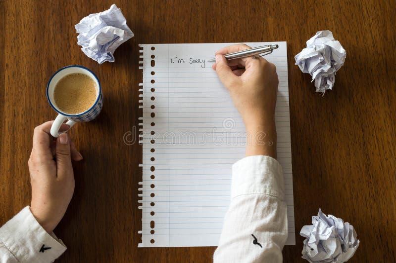 Lo siento escrito en el papel con café en las manos de madera de la tabla de una persona imágenes de archivo libres de regalías