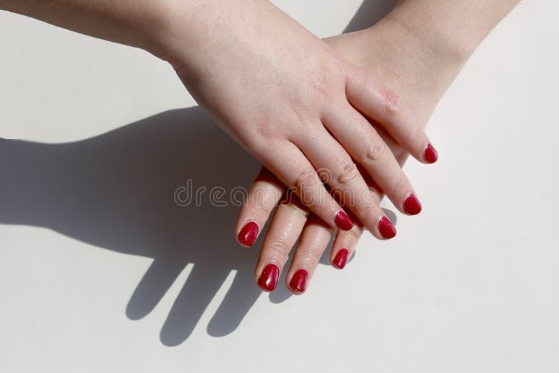 Lo smalto rosso dipinto a mano della donna alla moda, sovrapposizione di una mano d'altra parte fotografia stock libera da diritti