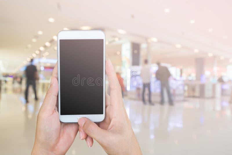 Lo Smart Phone della tenuta e della donna con il backgrou del centro commerciale della sfuocatura fotografie stock