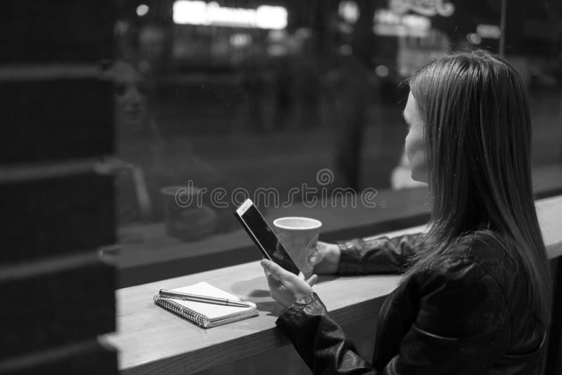 Lo smartphone della tenuta della ragazza a disposizione, si siede in caffè, il funzionamento, la penna, uso Rete, wifi, sociale,  fotografia stock libera da diritti