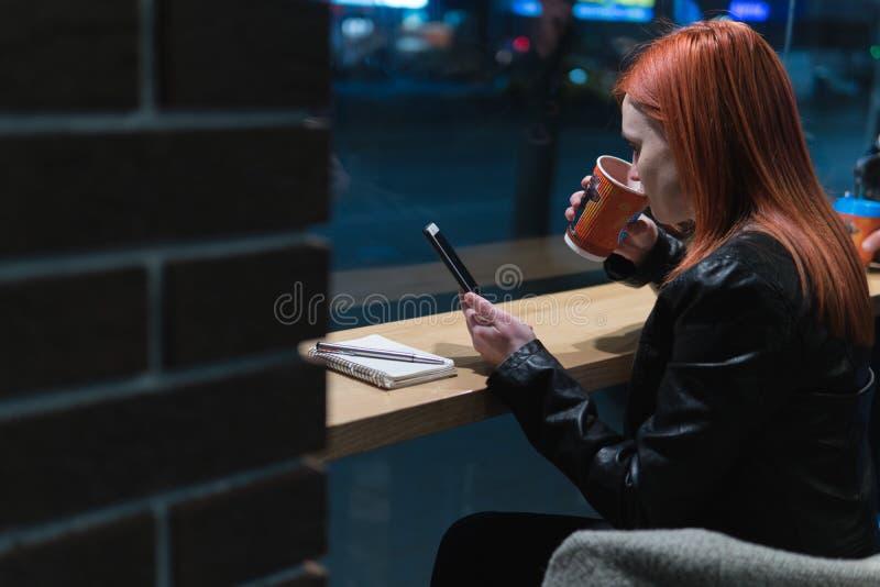 Lo smartphone della tenuta della ragazza a disposizione, si siede in caff?, il funzionamento, la penna, aggeggio di uso Rete, wif fotografia stock