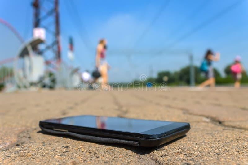 Lo smartphone perso si trova sulla strada in un parco pubblico fotografie stock libere da diritti
