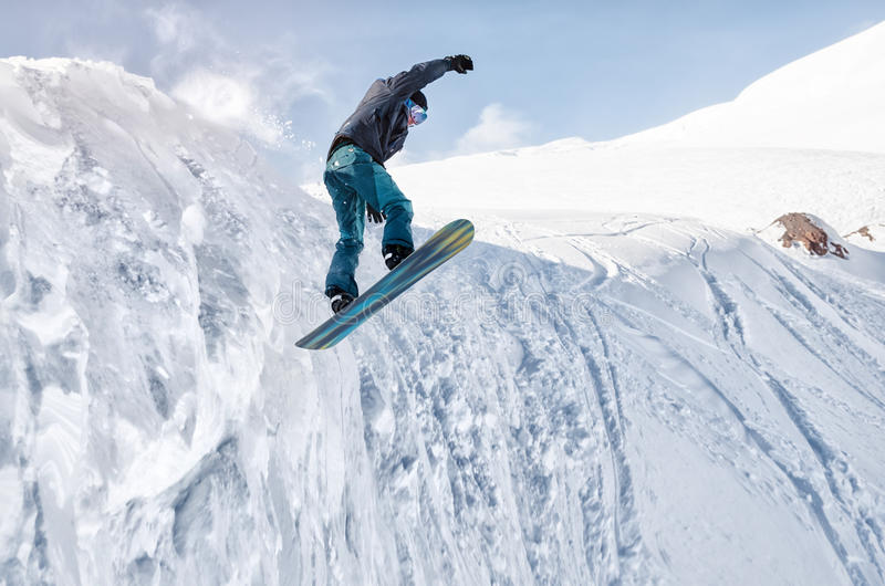 Lo snowboarder alla moda con il casco e la maschera salta dall'alto pendio della neve fotografia stock