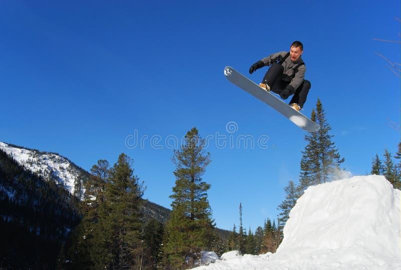 Lo Snowboarder che salta su immagini stock libere da diritti