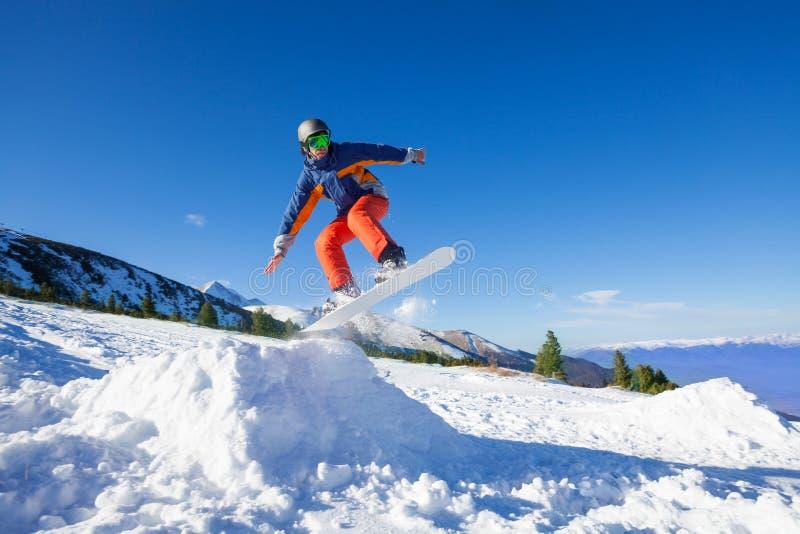 Lo Snowboarder che salta su dalla collina nell'inverno fotografia stock